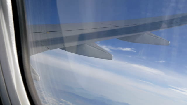 Wing of the plane flies over beautiful clouds. View from the window video