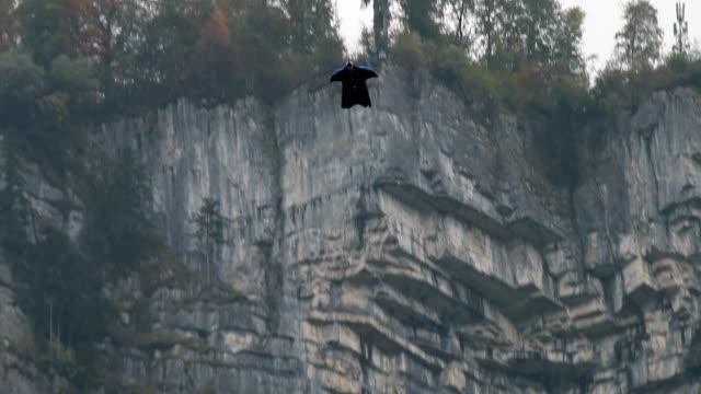 ala vola abito scende dalla scogliera, mirare a valle sottostante - base jumping video stock e b–roll