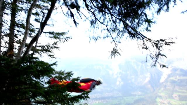 tuta ala vola scende dal bordo della scogliera - base jumping video stock e b–roll