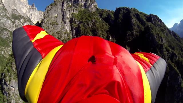 ala vola abito scende dalla scogliera di montagna - base jumping video stock e b–roll