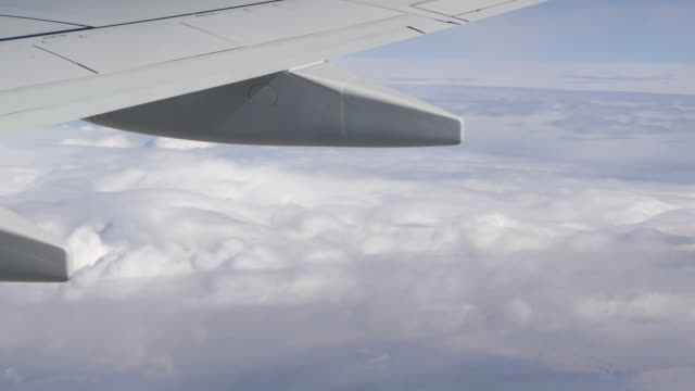 Wings of plane and clouds passing by video