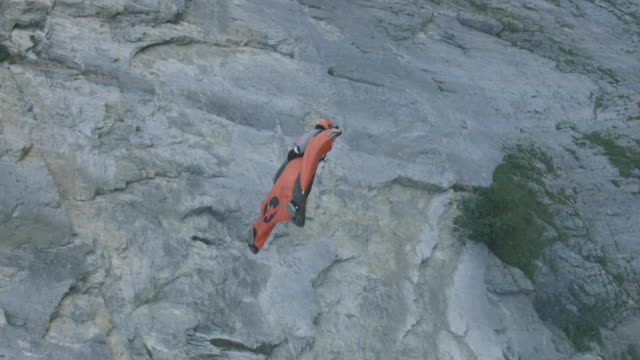 wingsuit flier jumps, then sail past rock cliff aerial flight - base jumping video stock e b–roll