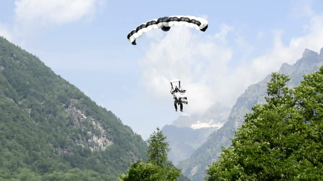 wingsuit flier lands with parachute in mountain meadow - base jumping video stock e b–roll