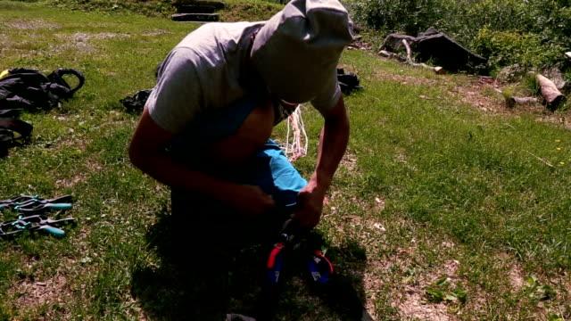 wingsuit flier packs canopy carefully in landing meadow - base jumping video stock e b–roll