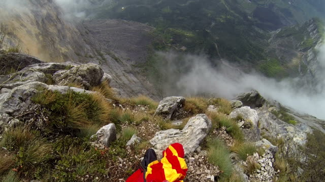 Wingsuit flier prepares to descend from cliff, mountains video