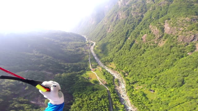 vidéos et rushes de wingsuit flier steers parachute towards landing area - base jump