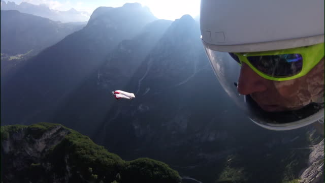 pov of wingsuit pilot flying over mountains and cliffs - coraggio video stock e b–roll