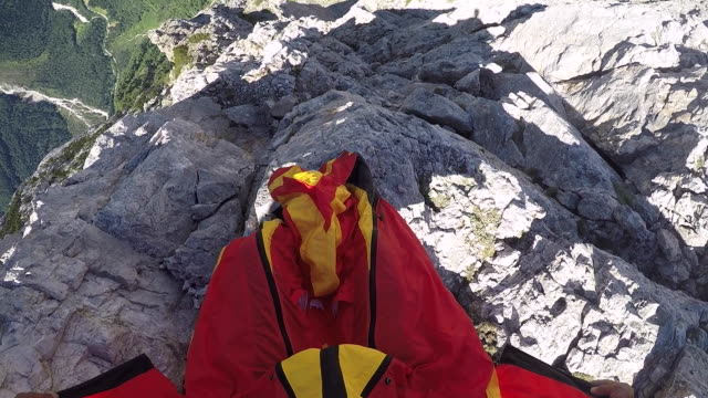 pov of wingsuit pilot jumping off rocky cliff - base jumping video stock e b–roll