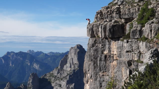 wingsuit pilot jumps off cliff - base jumping video stock e b–roll