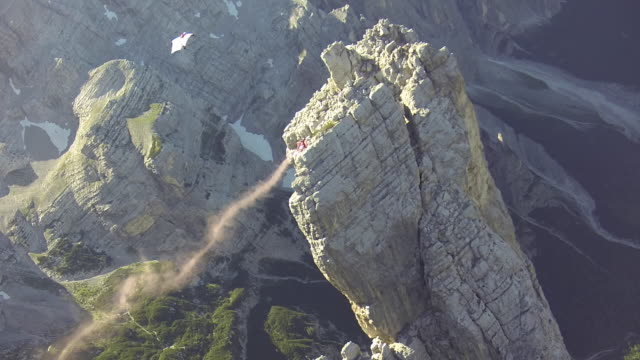wingsuit pilots fly close to cliff - base jumping video stock e b–roll