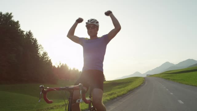 sun flare: winner of road race cheerfully pumps his arms and cycles no handed. - vincere video stock e b–roll