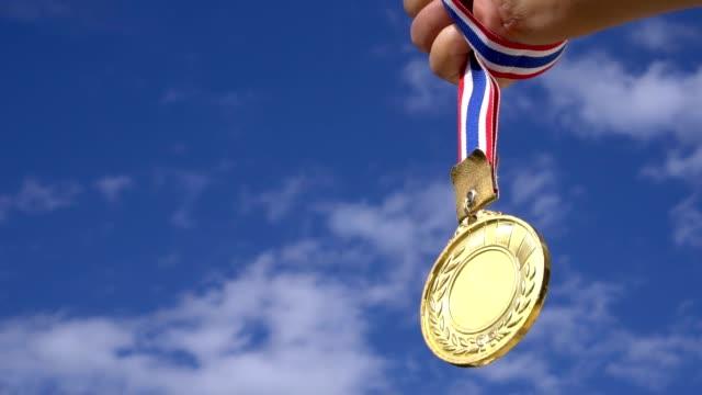 成功賞概念で勝者のチャンピオン: ビジネスマンの手に発生青空背景ビデオ スポーツやビジネス、スローモーションでの成功を表示するリボンの金目たるを開催 - メダル点の映像素材/bロール