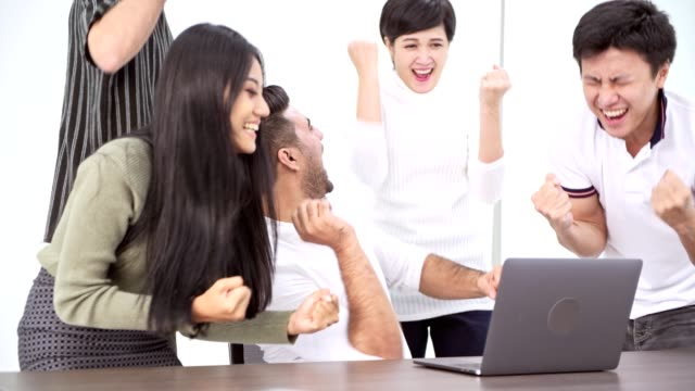 winning business team. asian businessman and woman with indian man looking at laptop and cheering for big win. successful start ups concept. - rischio video stock e b–roll