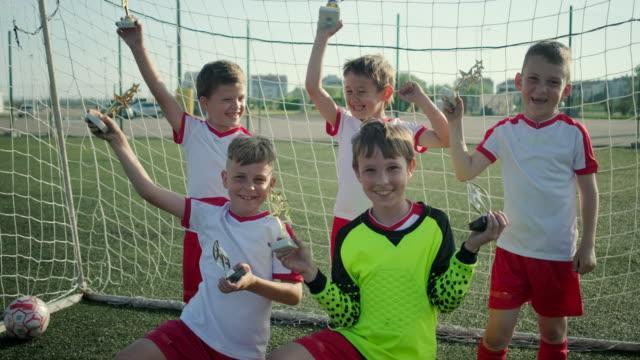 vídeos de stock, filmes e b-roll de a equipe de futebol de vencimento de meninos pequenos está demonstrando recompensas no stadium - troféu