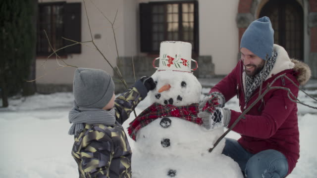 Winter Breaks Father and his 6 years old son making snowman. snowman stock videos & royalty-free footage