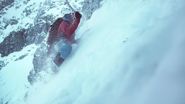 SLO MO winter climber swinging his axe to climb the snowy slope video