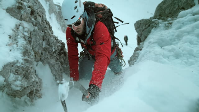 LD Winter climber using axe to ascend snow covered slope