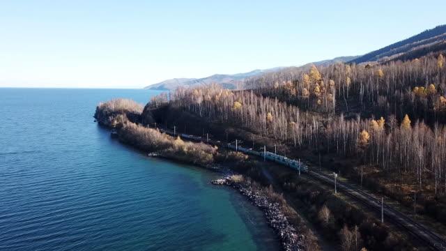vídeos de stock e filmes b-roll de winter day aerial drone follow trans-siberian railway passengers tourist train near baikal lake. cinematic professional footage. high altitude - lago baikal
