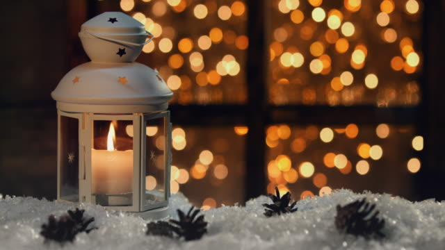 winter decoration with a candlestick near the snow-covered window - lanterna attrezzatura per illuminazione video stock e b–roll