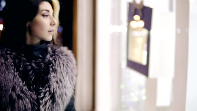 Winter dressed young woman comes up to the window display of expensive boutique store and stands in front of it. video