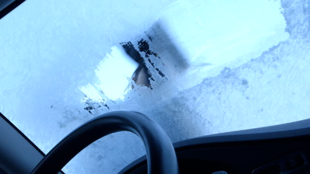 Winter Driving - Woman Scraping Ice from a Windshield video