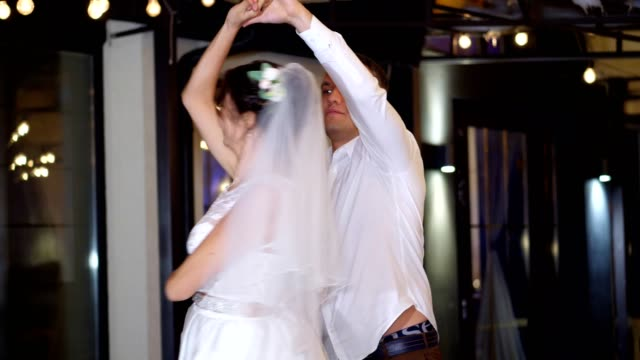 winter evening, a terrace decorated with light bulbs, in the street, the newlyweds are dancing their first wedding dance, a waltz. winter wedding - vídeo