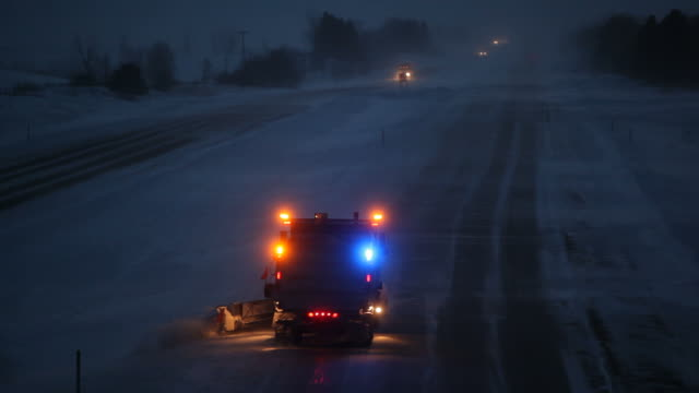 Winter Evening Interstate Highway with Blowing Snow and Plow An Interstate highway, shot on a winter evening with blowing snow and blizzard conditions. A snowplow is in the left lane, with ice visible on the road surface. plow stock videos & royalty-free footage