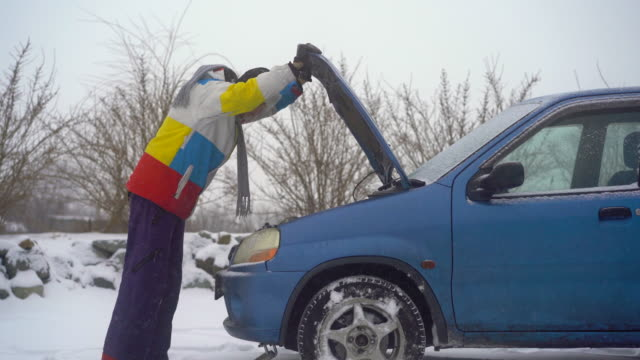 Winter, falling snow. Man on the road have troubles with his car. He is trying to find problem with an engine