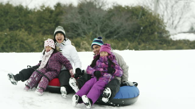 Winter Fun Family fun in the winter sledding with tubes on snow. recreational pursuit stock videos & royalty-free footage