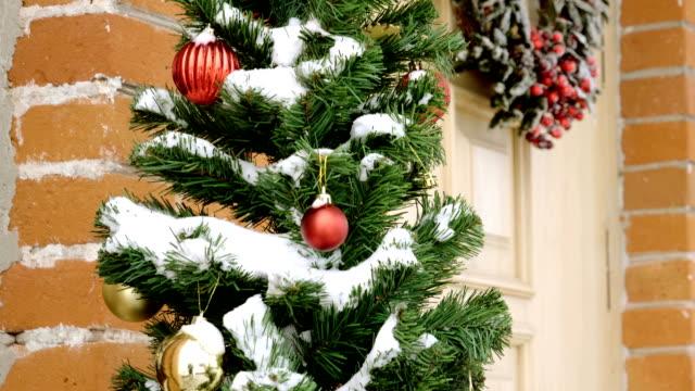 vídeos y material grabado en eventos de stock de vacaciones de invierno. corona de navidad colgando en la puerta principal de madera. a cámara lenta. hd - ornamentado