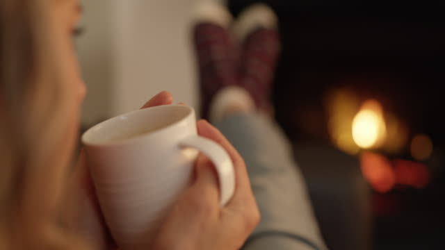 Winter is a time for comfort 4k video footage of a young woman having coffee while relaxing at home comfort stock videos & royalty-free footage
