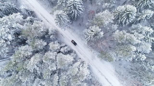 vídeos y material grabado en eventos de stock de paisaje de invierno. vista aérea del camino en invierno con el coche rojo en él - nieve amontonada