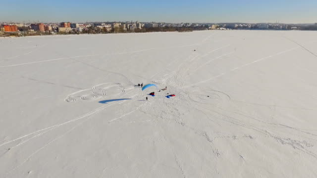 Winter landscape. Beautiful view of the winter city and the lake from a bird's-eye view. preparation of paragliders for competitions video