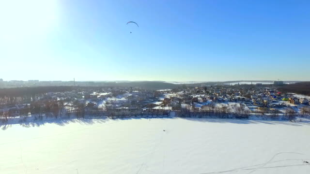 Winter landscape. Beautiful view of the winter city and the lake from a bird's-eye view. paraglider is flying over a frozen lake video