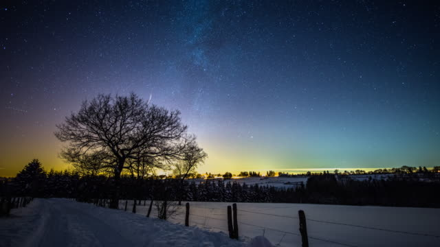 Winter landscape under starry night sky with milky way - Time Lapse video