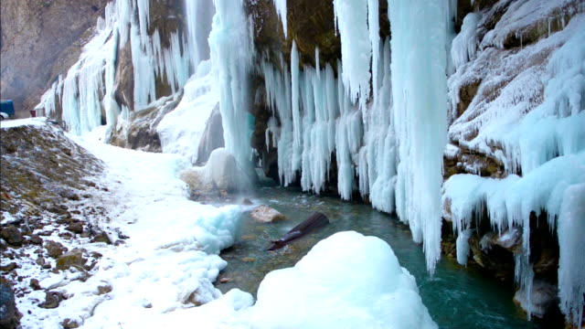winter landscape with cascade framed by blue icicle and turquoise river, Russia video