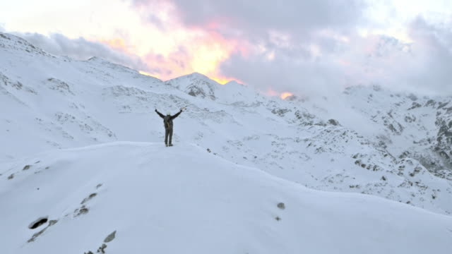 AERIAL Winter mountaineer victoriously raising his hands on mountain top video
