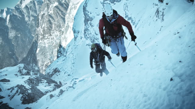 SLO MO winter mountaineers progressing up the snow capped mountain