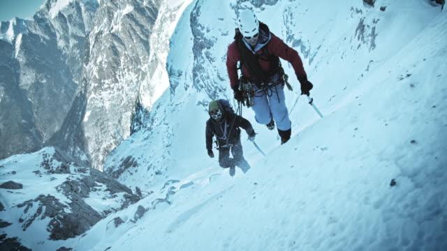 slo mo winter альпинистов прогрессирующую до на горы, покрытые снегом - альпинизм стоковые видео и кадры b-roll