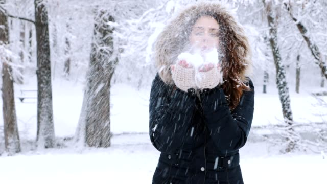 Winter portrait of a woman blowing a hanful of snow in front of the camera video