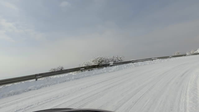Winter snow dangerous drive uphill on mountain rural curvy road video