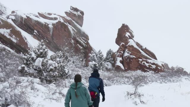 inverno racchette da neve coppia escursione nella neve rocce rosse parco morrison colorado - red rock video stock e b–roll