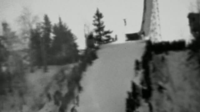 1937: Winter snowski jumping competition crowd lines steep hill. video