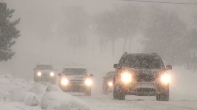 Winter snowstorm. Car traffic on slippery road. video