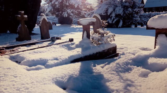 Winter sunlight on snow covered tombstones video
