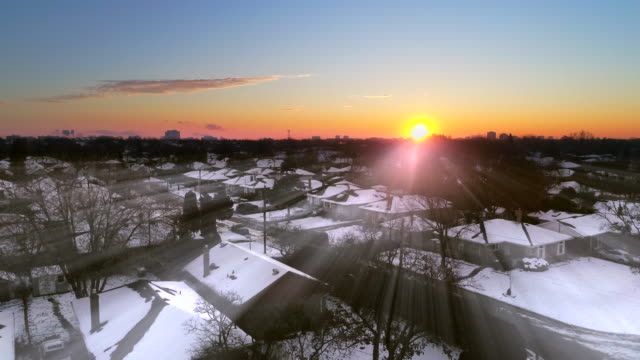 Winter sunrise over an urban area Beautiful dawn in a suburban area of Toronto, Canada during the Winter season. The sky has diverse colors and the rooftops of the houses are covered in snow winter stock videos & royalty-free footage