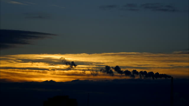 Winter sunrise over the city. Smoke belching from the chimney. Strong wind drives dark clouds. Time  lapse  footage. video