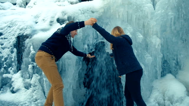 Winter waterfall. Fast stream water. Frozen water video