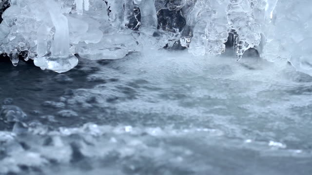 Winter waterfall with ice forms and iciclels. Flowing water on river with ice in cold season. video