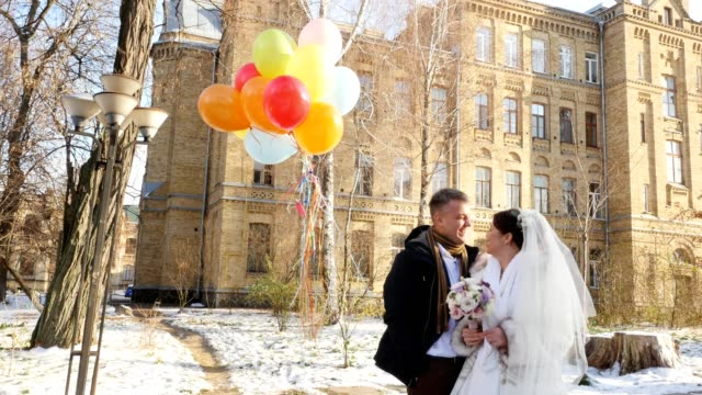 winter wedding, happy, laughing newlyweds with bright, multi-colored balloons. sunny snowy day, the ancient architecture of the city